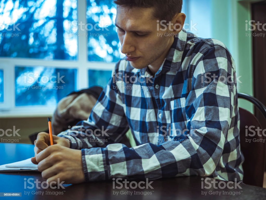 scientist at the table writing in notebook discover new technology checkered shirt - Royalty-free Adult Stock Photo