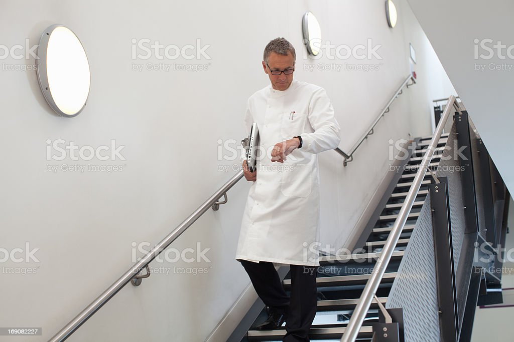 Scientist checking his watch on stairs stock photo
