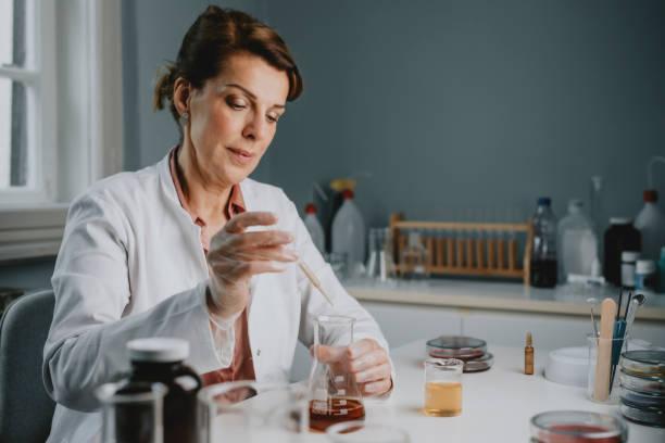 vetenskapsman / kemist i en vit lab coat med hjälp av en dropper att lägga till något till en erlenmeyer kolv på ett labb - laboratory add flask bildbanksfoton och bilder