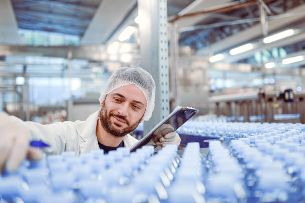 scientist controller doing revision in bottling plant - bottling plant stock photos and pictures