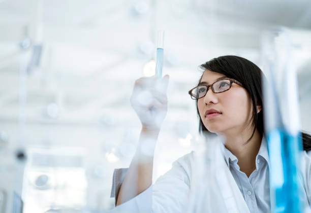 Scientist doctor looking at sample in test tube stock photo