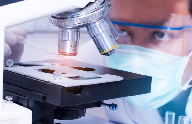 scientist droping liquid to the slide with microscope in laboratory room. scientific research - ematologia foto e immagini stock