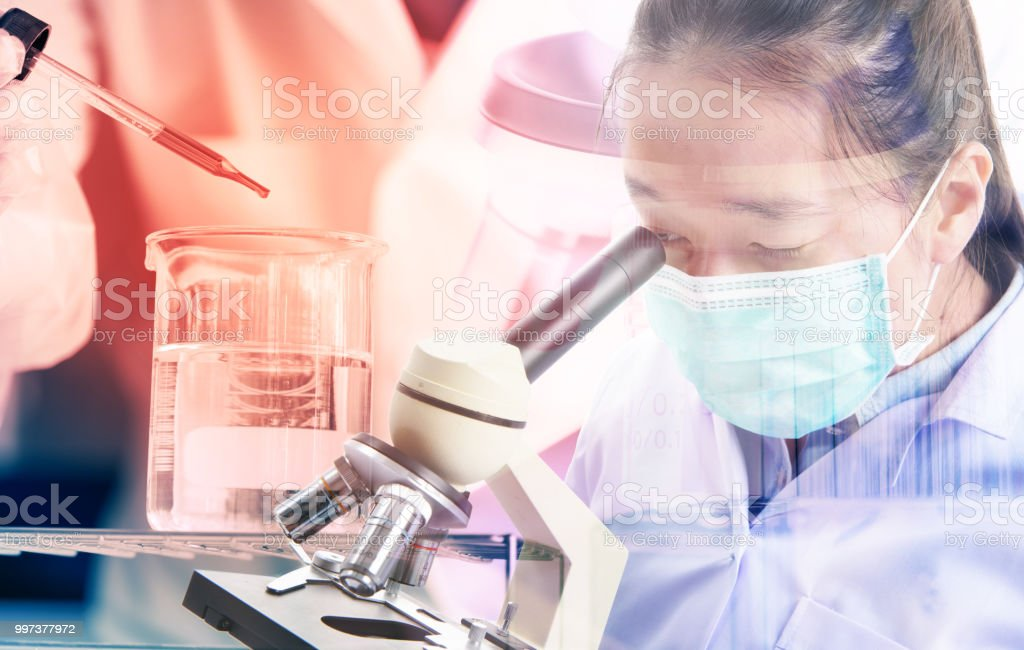 scientist dropping chemical liquid to flask with microscope double...