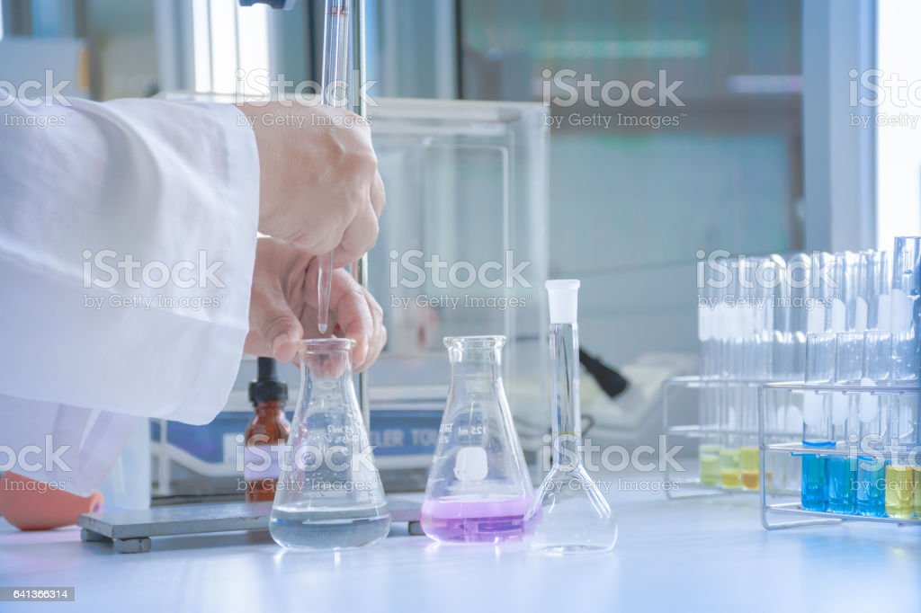Scientist dropping sample in flask stock photo