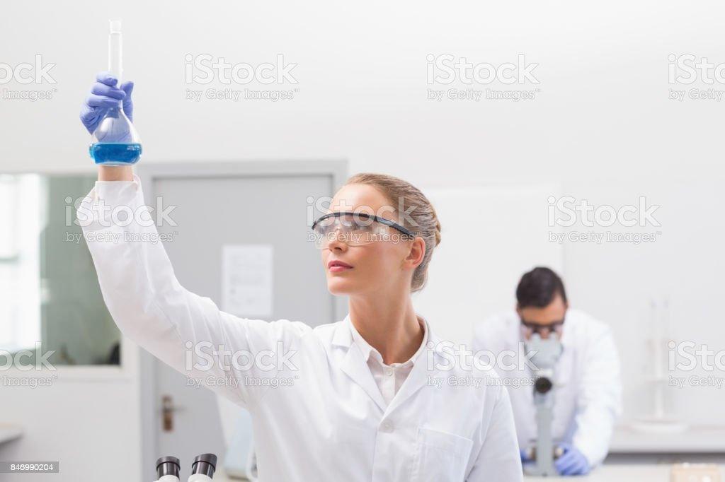 Scientist examining blue precipitate in baker stock photo