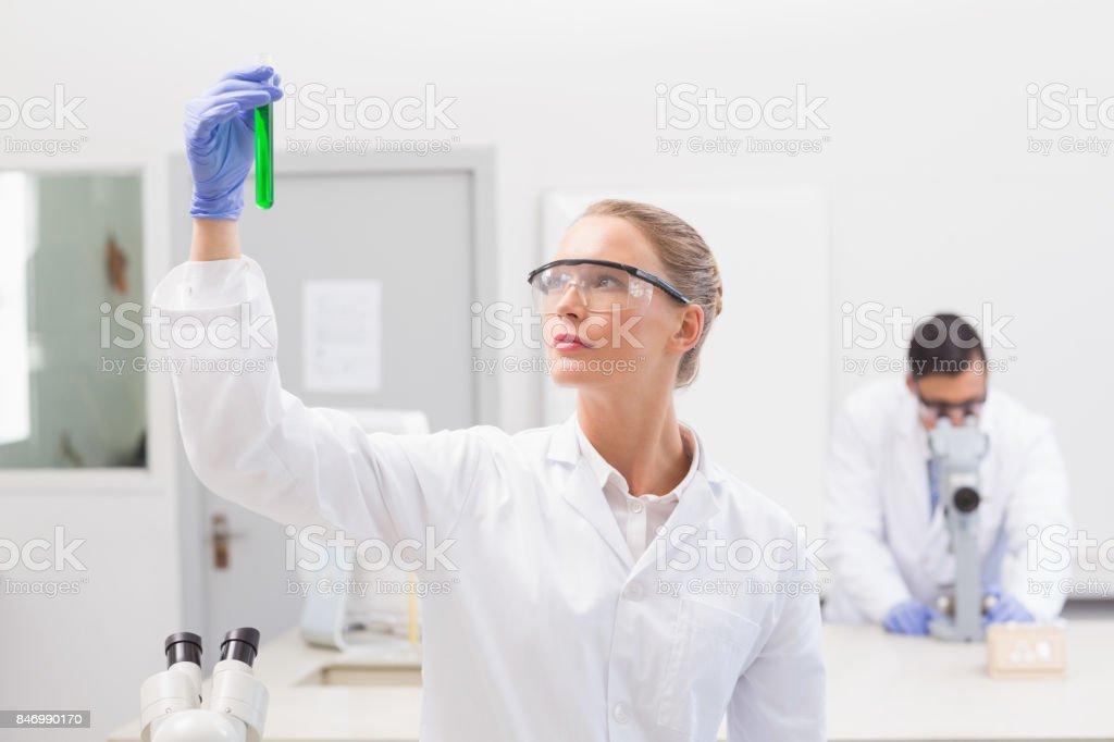 Scientist examining green precipitate in tube stock photo