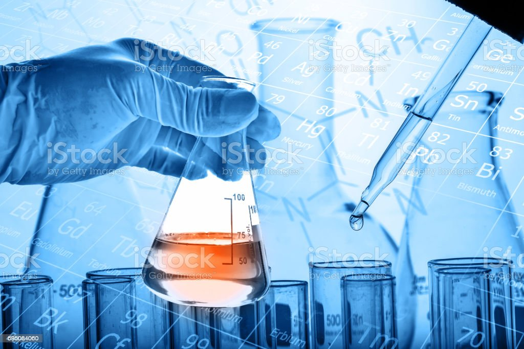 Scientist hand holding flask with test tubes background stock photo