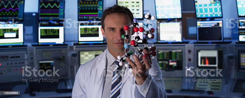 Scientist holding molecule model in control room royalty-free stock photo