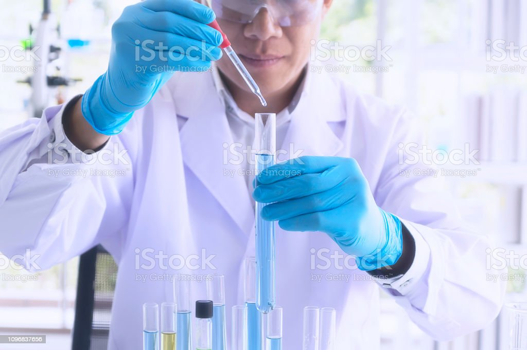 Scientist holding sampling oil or chemical liquid in flask with lab...