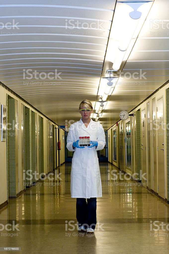 Scientist holding test tube rack walking in hallway stock photo
