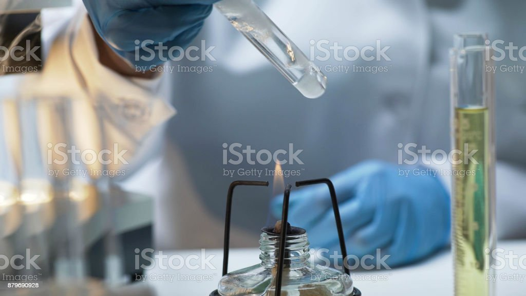 Scientist holding tube with boiling fuming liquid over burner, lab experiment stock photo