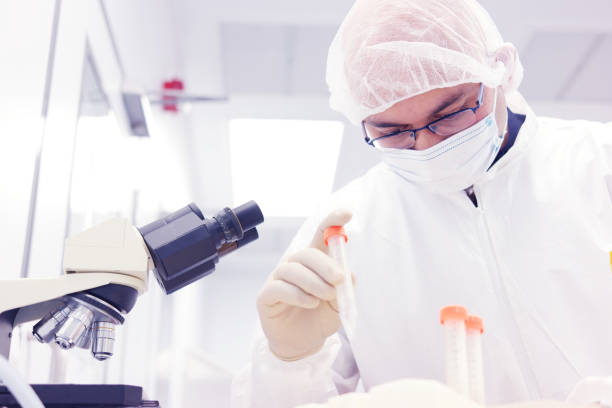 scientist in a clean room - white suit stock photos and pictures