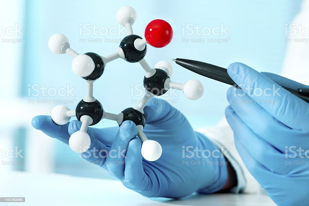 Scientist in blue latex gloves pointing a pen to a molecule stock photo