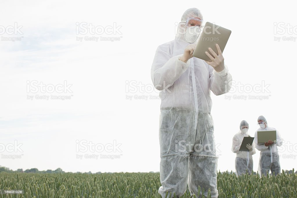 Scientist in protective gear using tablet computer stock photo