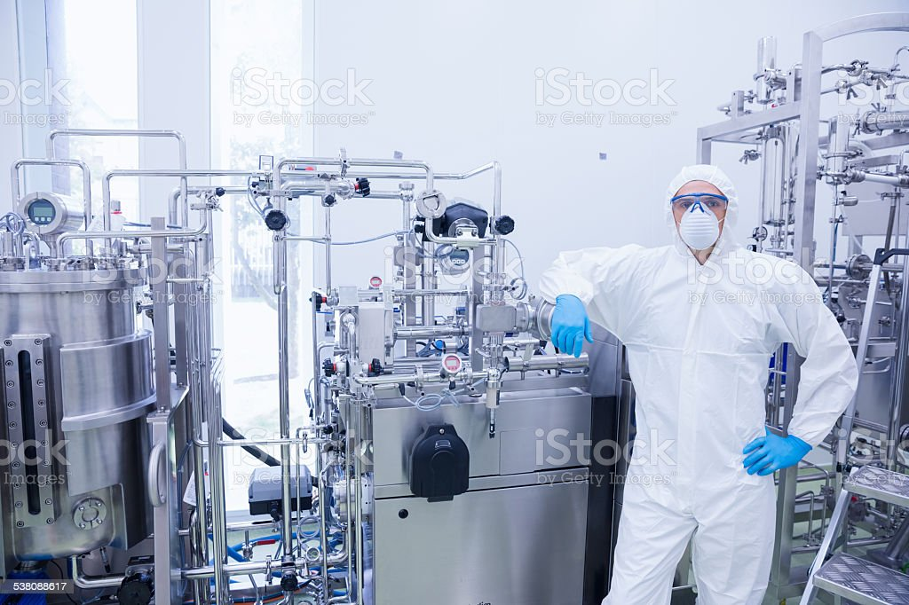 Scientist in protective suit leaning against machine stock photo