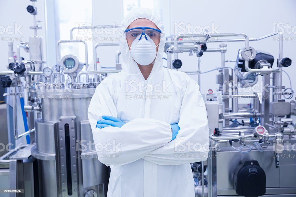 Scientist in protective suit standing with arms crossed stock photo