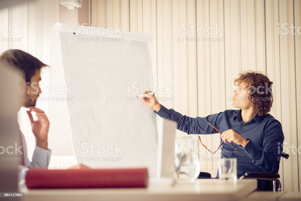 Scientist in wheelchair holding presentation royalty-free stock photo