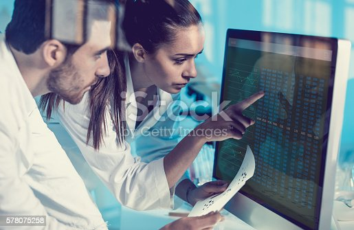 istock Scientist Interacting With the Computer Via Touch Screen 578075258