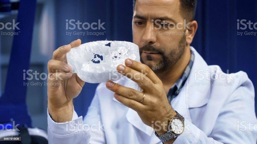 Scientist investigating 3-D printed cranium stock photo