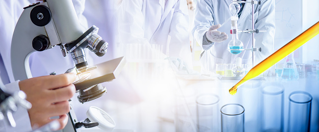 scientist lab technical service observe liquid sample with lab glassware, microscope and test tubes in chemical laboratory background, science laboratory research and development concept.