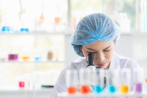 istock Scientist look throgh microscope. 1164295530