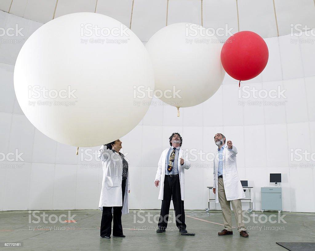 Scientist look upwards at balloons royaltyfri bildbanksbilder