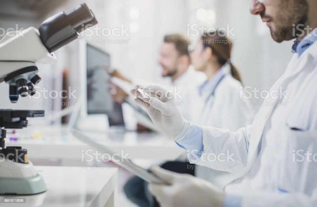 Scientist Looking at Microscope Slide stock photo