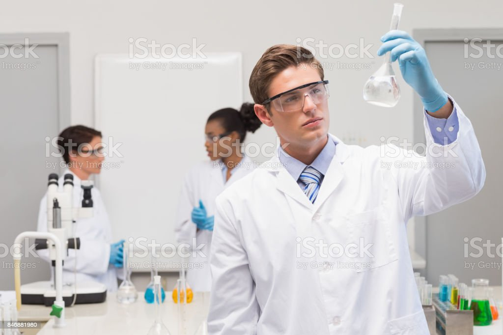 Scientist looking at white precipitate while colleagues talking together stock photo