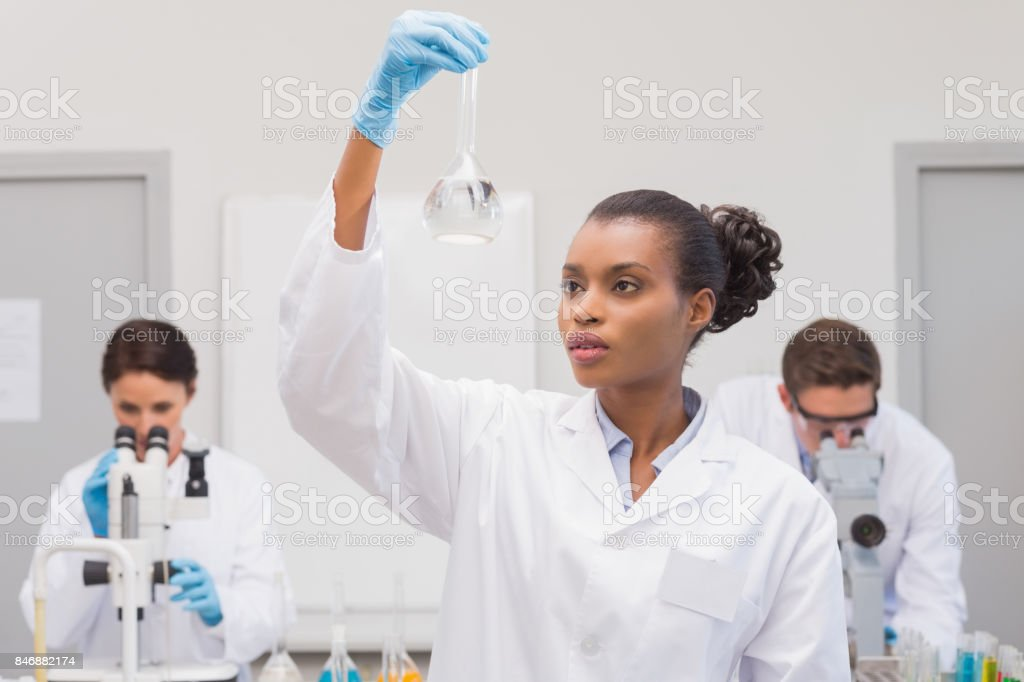 Scientist looking at white precipitate while colleagues working stock photo