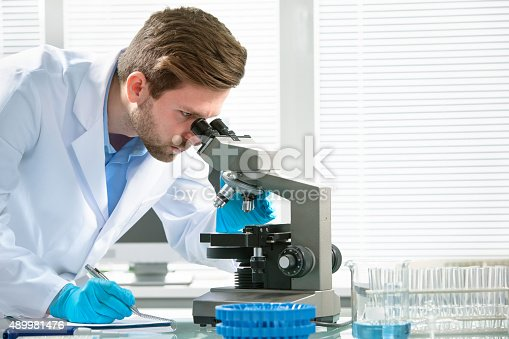 istock Scientist looking through a microscope 489981476