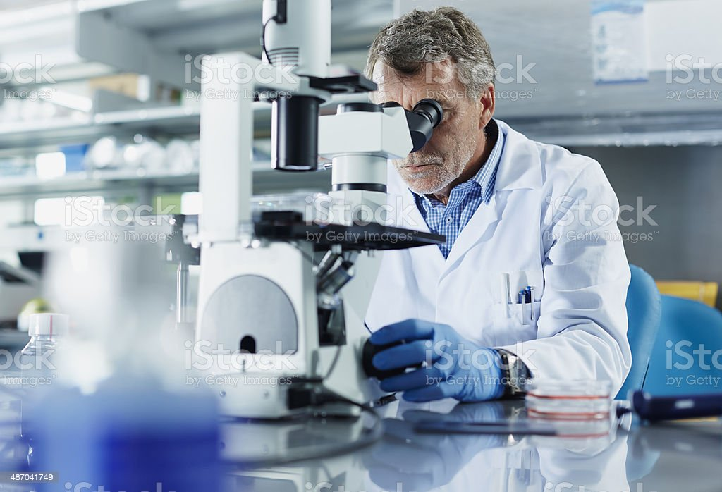 Scientist looking through microscope - foto de acervo