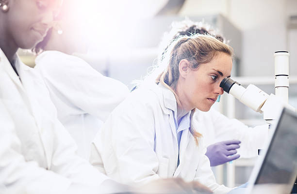 Scientist Looking Through the Microscope stock photo