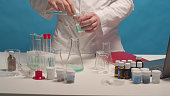 A chemist using a volumetric flask and a beaker mixes the preparations