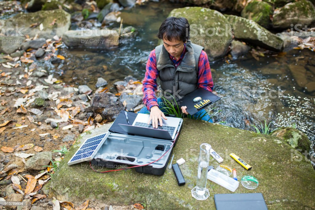 A scientist monitoring water quality from a solar powered field laboratory stock photo