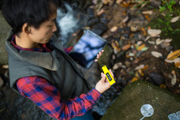 A scientist or researcher testing water quality with a pH meter stock photo