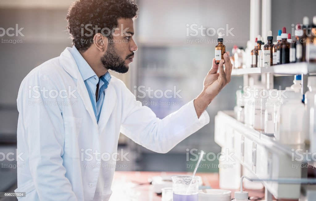 Scientist Picking up a Reagent From The Inventory stock photo