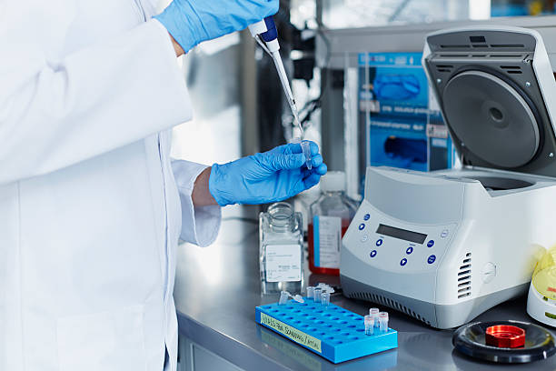 Scientist pipetting samples into eppendorf tubes Scientist pipetting samples into eppendorf tubes before doing centrifugation centrifuge stock pictures, royalty-free photos & images