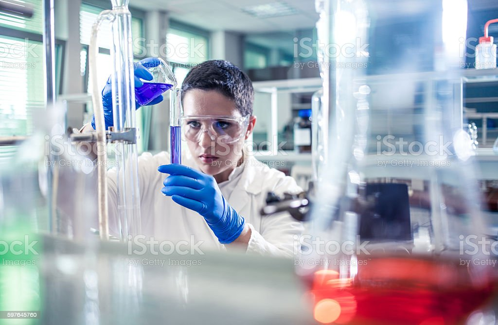 Scientist pouring a reagent into a measuring cylinder stock photo