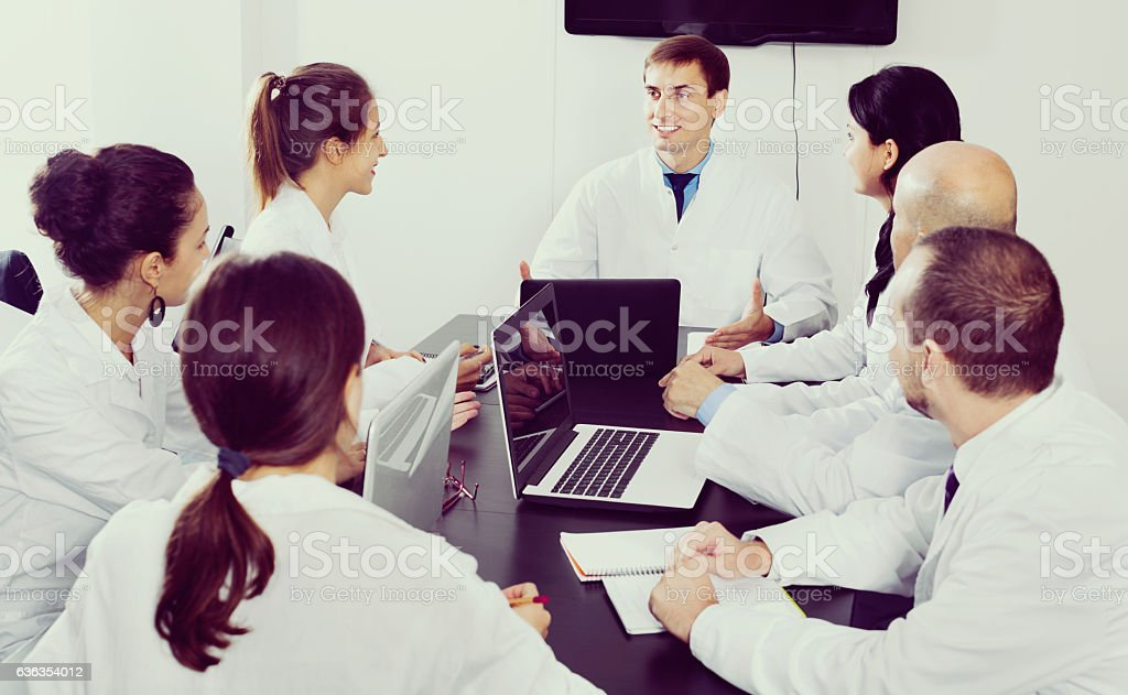 Scientist presenting report during working meeting stock photo
