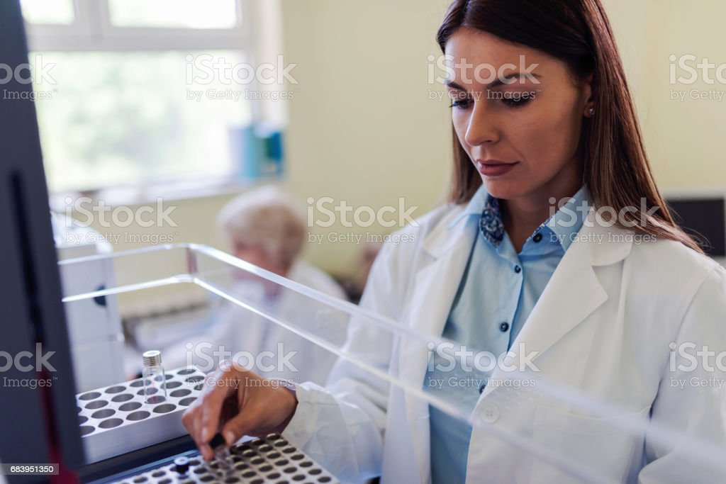 Scientist putting samples in research equippment. stock photo