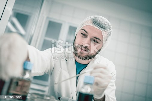 Scientist Reaching For Bottle Containing Ingredient Needed To Make Compound