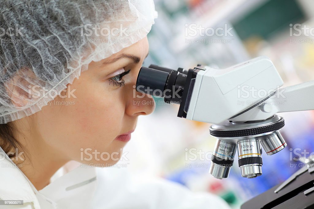 Scientist researcher looking into a microscope royalty-free stock photo