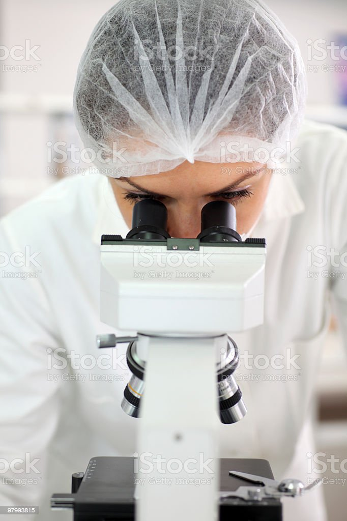 Scientist researcher looking into a microscope. royalty free stockfoto