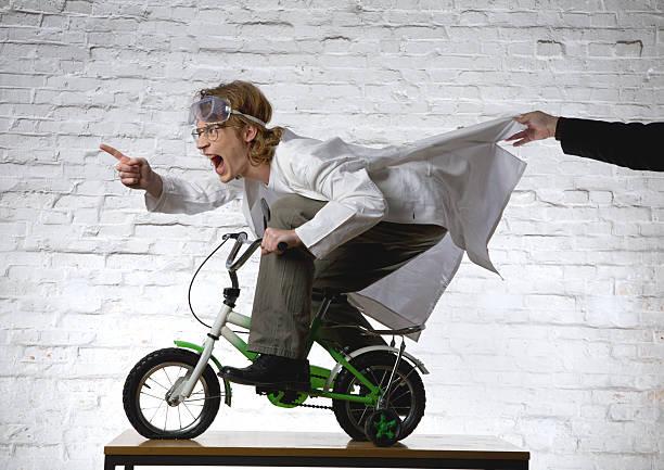 Scientist Riding Mini Bike While Person Grabs His Lab Coat stock photo