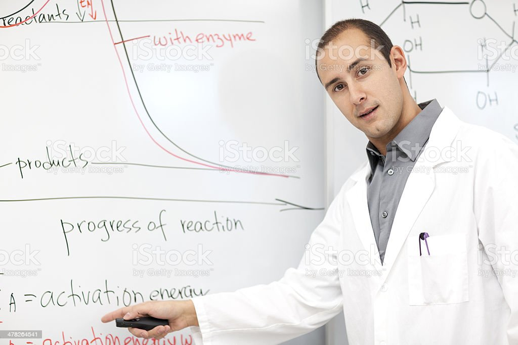 Scientist standing by the white board covered with graphs stock photo