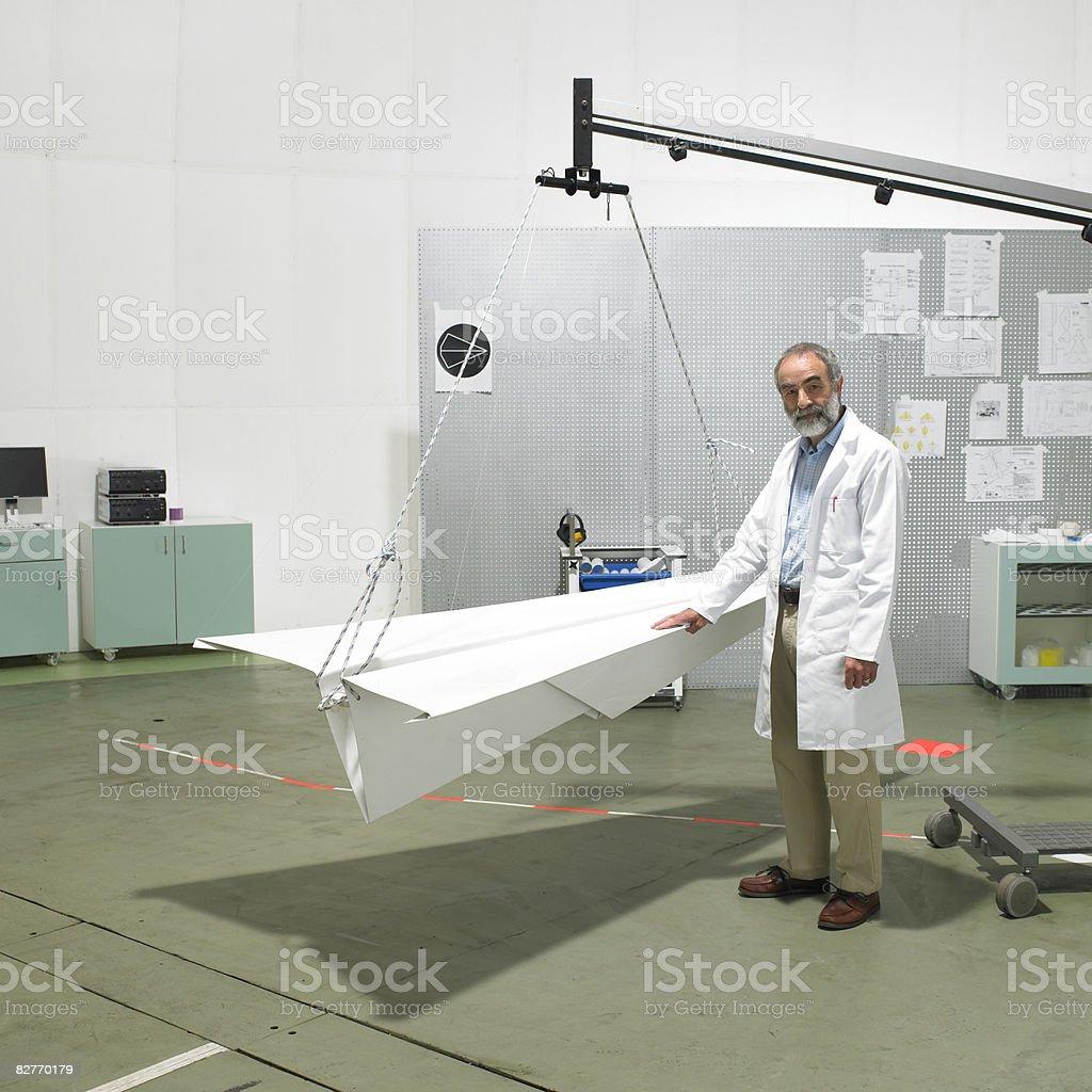 Naukowiec stojący w laborator z papierowy Samolot zbiór zdjęć royalty-free