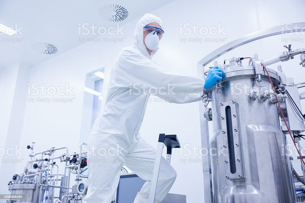 Scientist standing on ladder looking at the camera stock photo