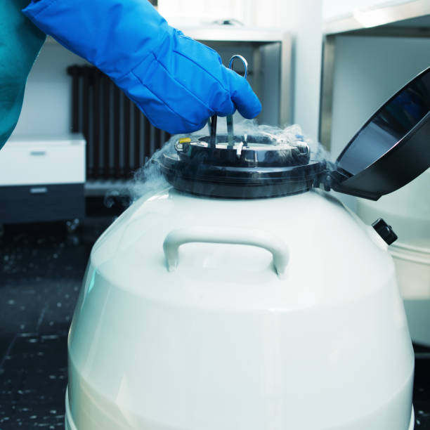 Scientist storing a sample in a canister Scientist storing a sample in a canister liquid nitrogen stock pictures, royalty-free photos & images
