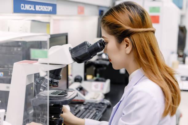 scientist using a microscope in a laboratory - medical technology стоковые фото и изображения