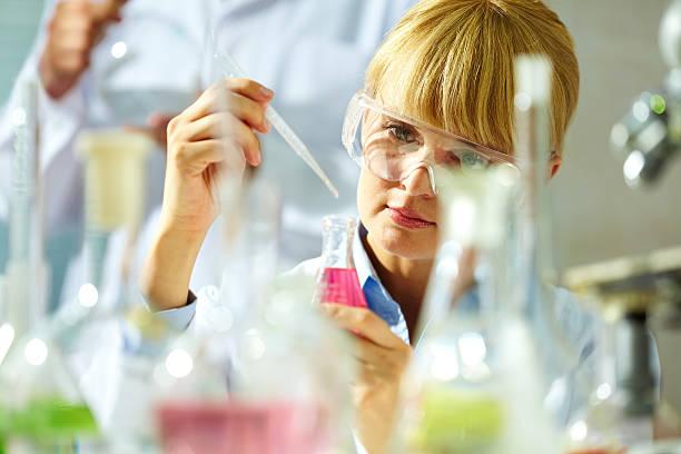 a scientist using a pipette to add liquid to a bottle - laboratory add flask bildbanksfoton och bilder